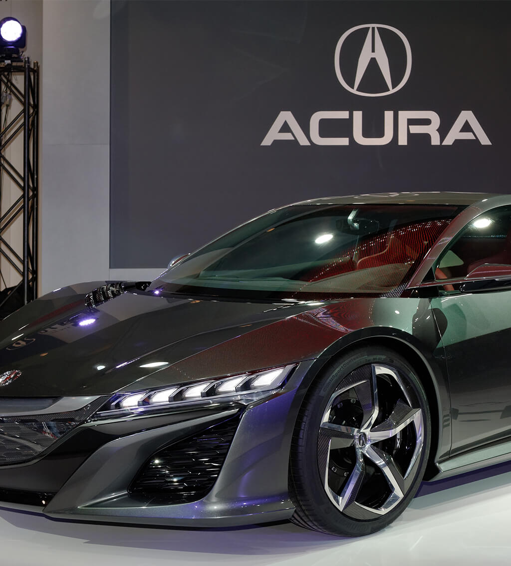 A gray Acura 2021 ILX luxury car displayed in front of a large Acura logo