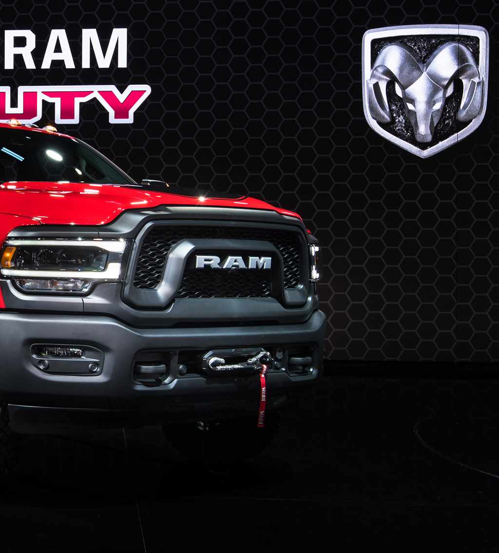 Front of a red Dodge Ram Truck with the Dodge logo at the background