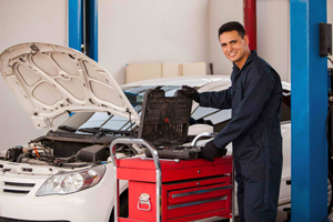 An auto repair technician opening a toolbox for car repairs and a white sedan with opened hood in the background