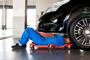 Auto technician on a mechanic's creeper, repairing the underside of a black car