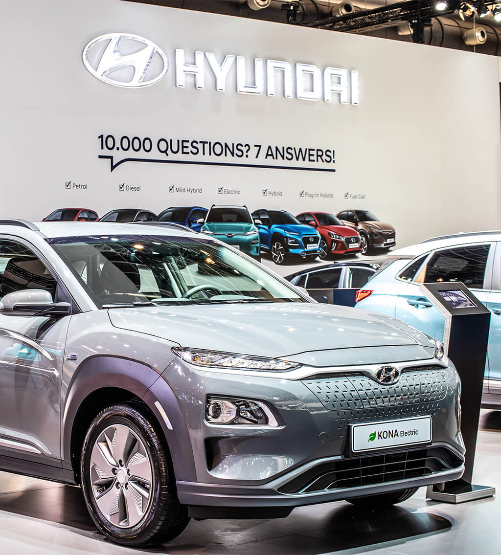 A gray 2021 Hyundai Kona electric car displayed with other vehicles from the company