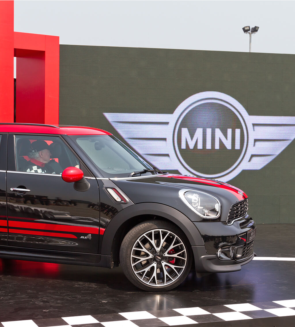 Side view of a black MINI All-Wheel Drive with red highlights and a large MINI logo at the background
