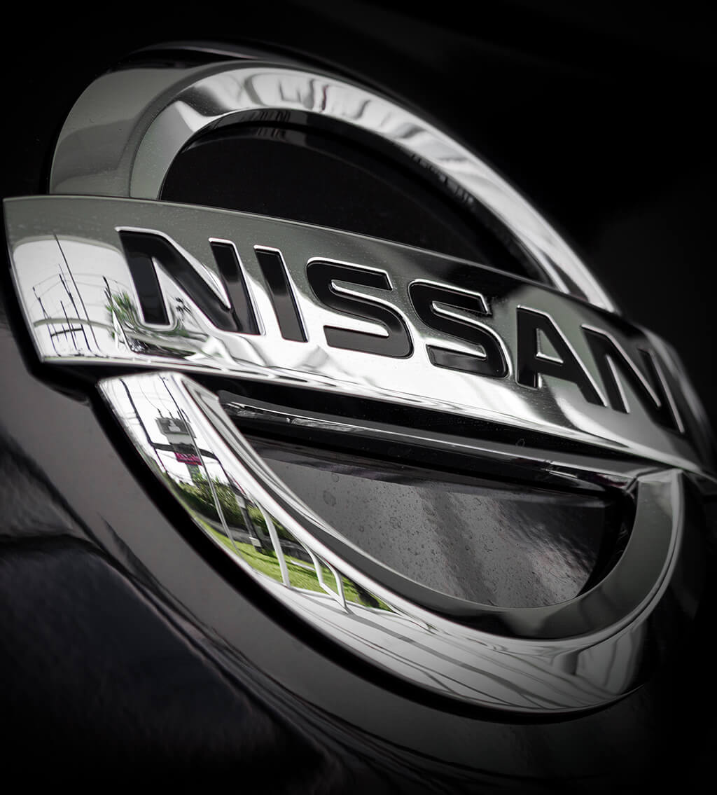 Extreme close-up of the metal Nissan logo on a black car