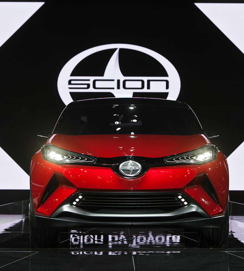 Front view of a red Scion 2000s car with a large Scion logo at the background