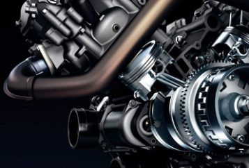 Close-up graphics of an automotive engine showing the flywheel and nearby pipes